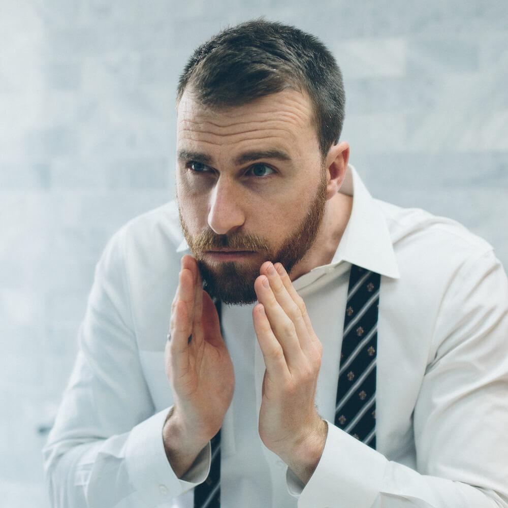 L'homme regarde sa barbe fraîchement coiffée